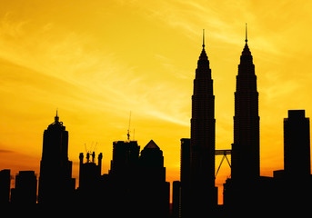 Silhouette of KLCC tower during golden sunrise