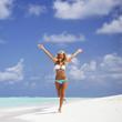 Woman in bikini running on the beach