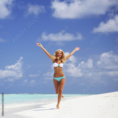 Woman in bikini running on the beach