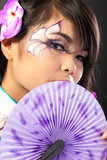 Beautiful asian woman wears a national dress is holding a fan