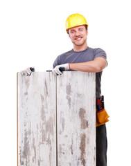 Smiling carpenter holding the floor panels