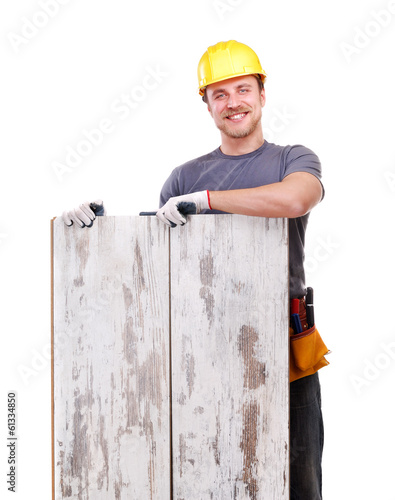 Smiling carpenter holding the floor panels