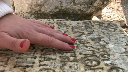 Woman hand touching ancient Greek inscriptionncient stone