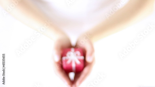 Hands Offering red gift box with white ribbon