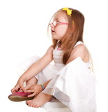 child little girl tries to put on her shoes isolated
