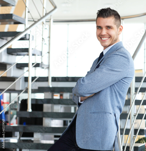positive business man standing on stairs of modern office