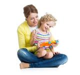 Mother and kid girl having fun with musical toy. Isolated on whi
