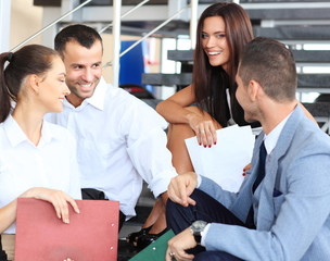 business partners sitting on stairs in office building and discu