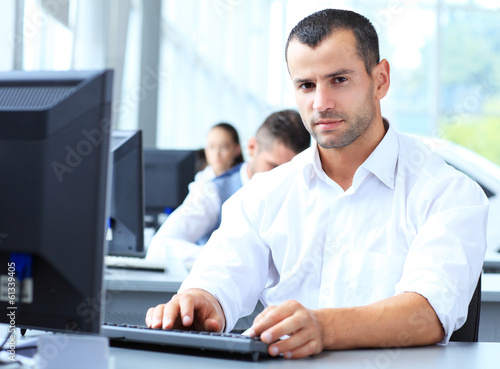 Casual businessman working in office, sitting at desk