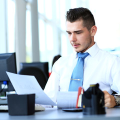 Happy businessman sitting and working in office