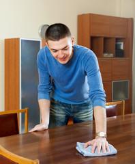 Smiling man polishing table with furniture polish