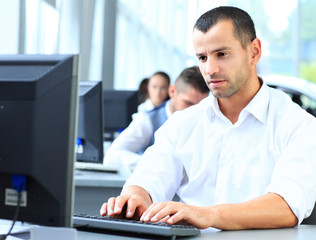 Casual businessman using laptop in office, sitting at desk