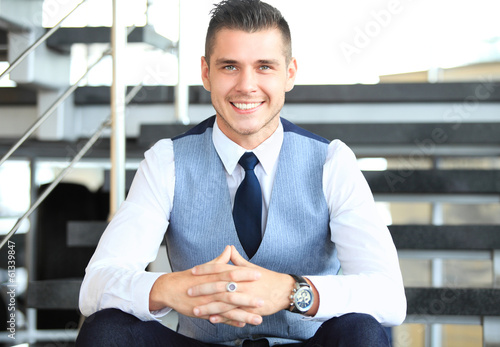 positive business man sitting on stairs of modern office
