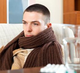 ill sad man in warm scarf