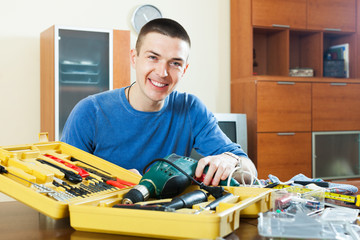 Happy smiling guy organizes tools on table