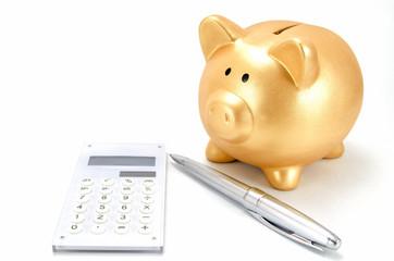 金色の豚の貯金箱と電卓とボールペン