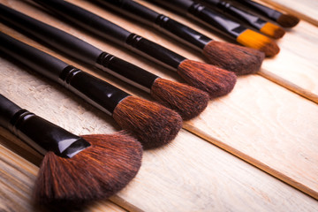 Set of black make-up brushes in row on the wooden table
