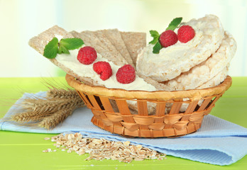 Tasty crispbread with berries in wicker basket, on green table