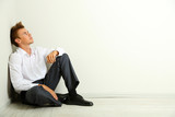 Young businessman  sitting on floor, on gray wall background