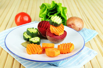 Beautiful sliced vegetables, on plate, on wooden background