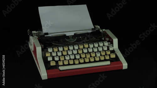 Vintage typewriter rotates on a black background loop