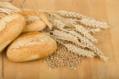 roll on wooden table with ears of wheat grain