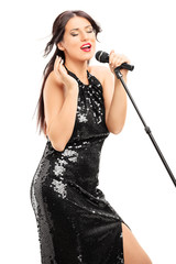 Beautiful woman in black dress singing on microphone