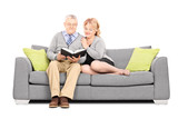Mature couple sitting on sofa and reading a book
