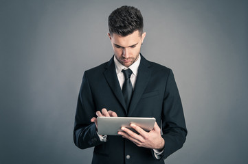 Young businessman looking at tablet against dark background.