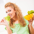 Beautiful young woman eating salad.