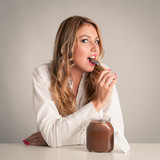 Blonde woman eating chocolate cream with teaspoon.