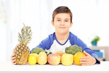 Smiling boy sitting at table full of fruits and vegetables
