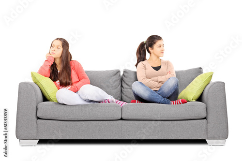 Two teenage girls sitting on sofa angry with each other