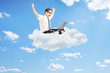 Businessman working on laptop and seated on cloud