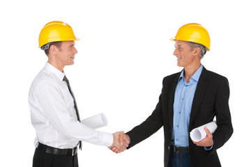 two workers shaking hands and smiling.