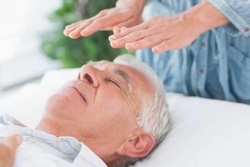 Therapist performing Reiki over senior man