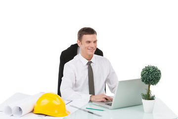 handsome male smiling and typing at computer.