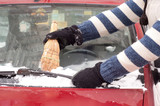 Car cleaning from snow with straw broom