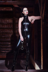Sexy woman in catsuit holding handcuffs