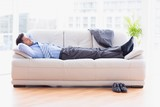 Tired businessman sleeping on a sofa