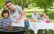 Father and son at barbecue grill with family having lunch in