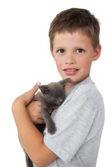 Little boy holding grey kitten smiling at camera