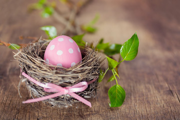 Easter egg in nest on wooden background
