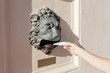 person lowers  letter in a mailbox in form of head of lion