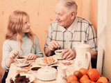 grandfather and granddaughter sitting on the table  in kitchen