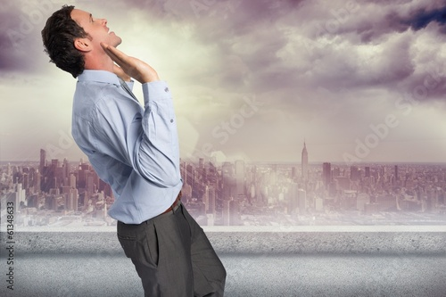 Composite image of businessman standing with arms pushing up