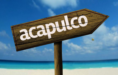 Acapulco, Mexico wooden sign with a beach on background