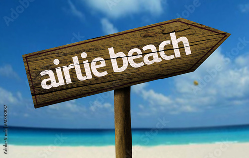 Airlie Beach, Australia wooden sign with a beach on background