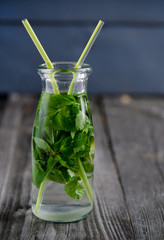 Drink of fresh mint in glass bottle on a wooden board