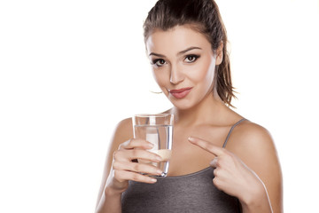 woman hold glass of water and shows her finger on a glass